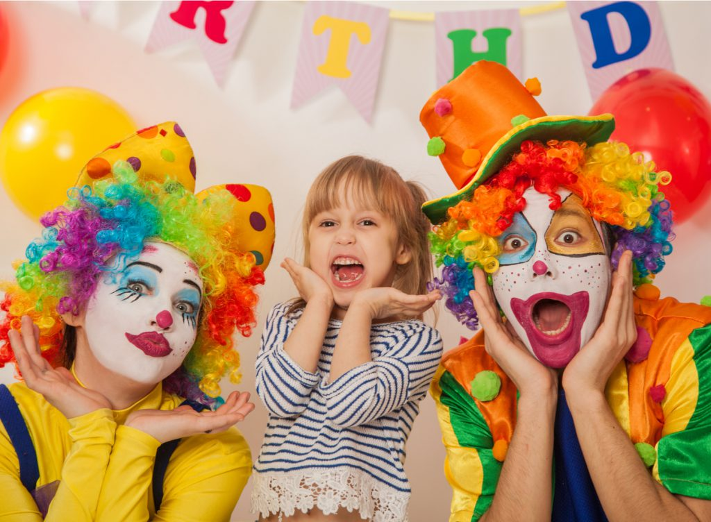 Two clowns and a girl posing at a Rico Kids birthday party