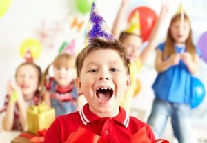 A little boy with a birthday hat shouting what is Rico Kids